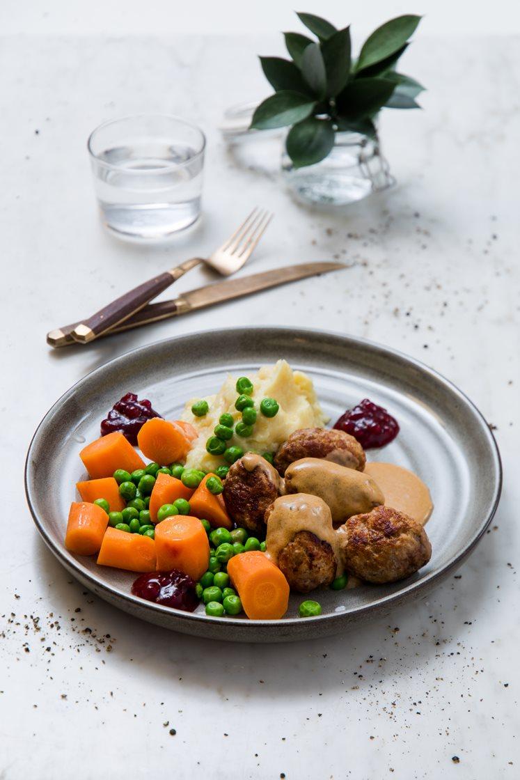 Kjøtt- og grønnsaksboller i fløtesaus med potetmos, kokte grønnsaker og rørte tyttebær