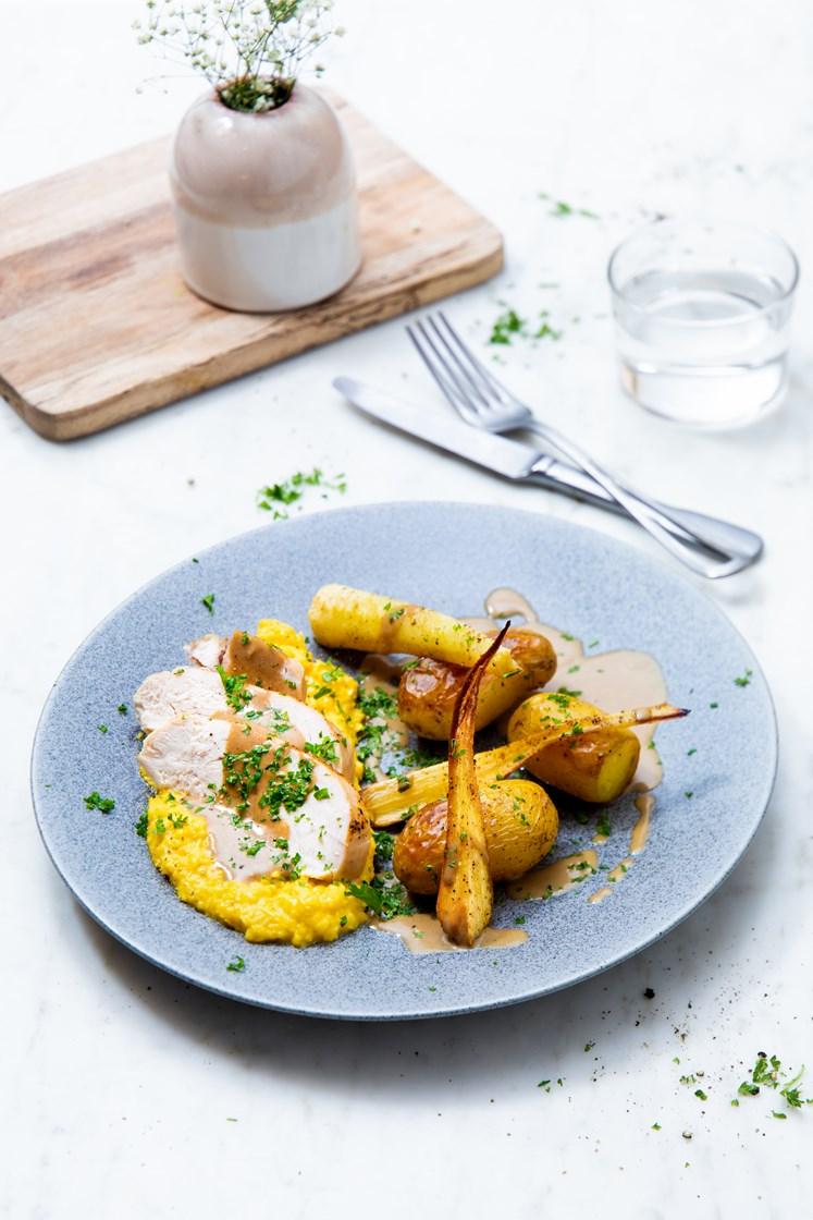 Kyllingbryst med maiskrem, ovnsbakte poteter og pastinakk, servert med steinsoppsaus