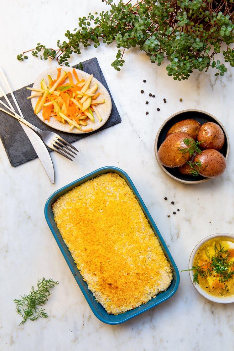 Fiskegrateng med kokte poteter og råkostsalat med eple, servert med eggesmør