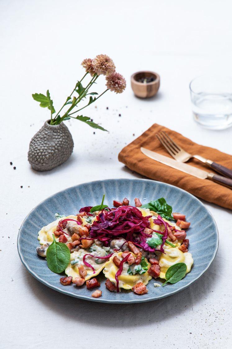 Steinsoppravioli med sjampinjong i kremet spinatsaus, toppet med sprøstekt bacon og syrlig rødkål