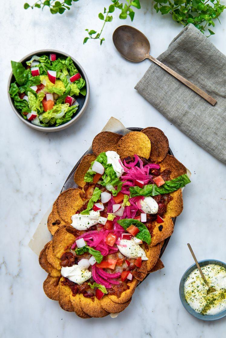 Gratinerte nachos med chili con carne, toppet med syltet rødløk, salat og hvitløksdressing