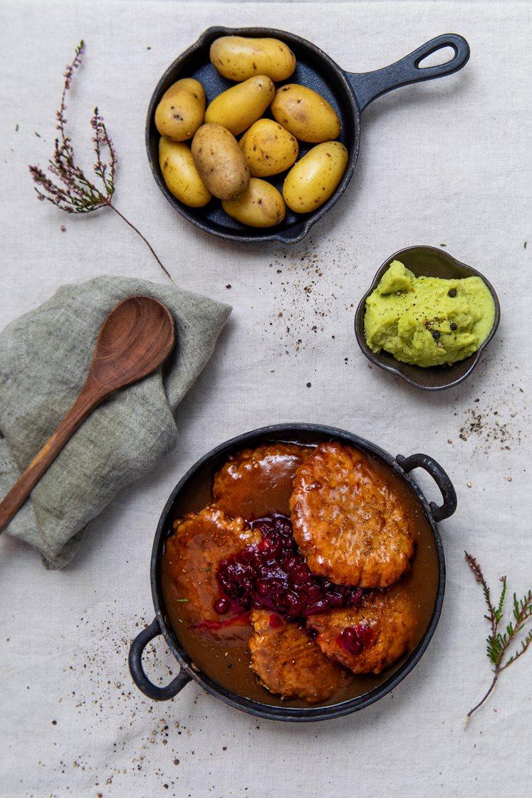 Grove karbonader i brun saus med kokte poteter, ertestuing og rørte tyttebær