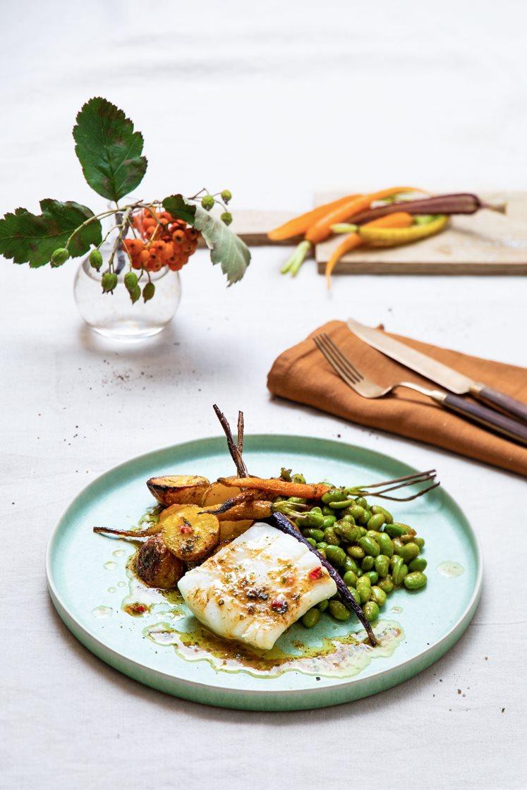 Kokt torsk med ovnsbakte gulrøtter og poteter, servert med edamamebønner i kryddersmørsaus