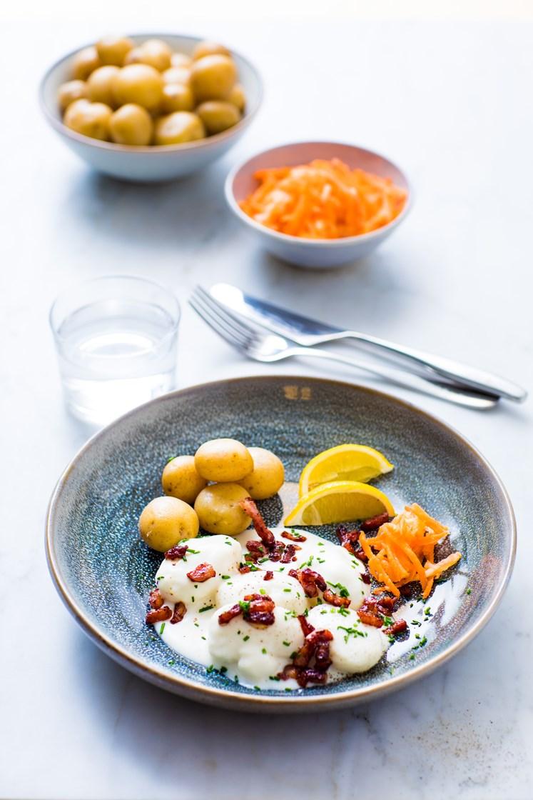Fiskeboller i hvit saus med kokte poteter, råkostsalat med appelsin og sprøstekt bacon