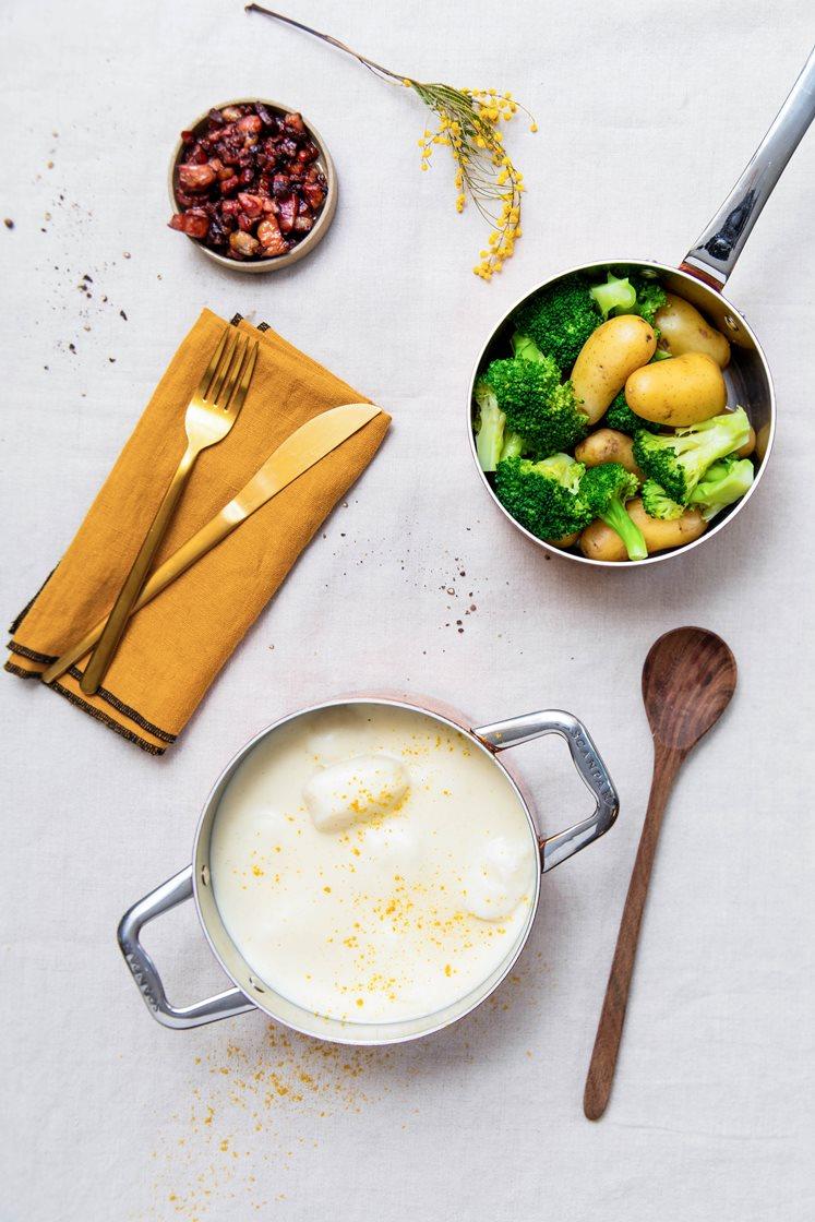 Fiskeboller i hvit saus med småpoteter og brokkoli, servert med sprøstekt bacon og karri