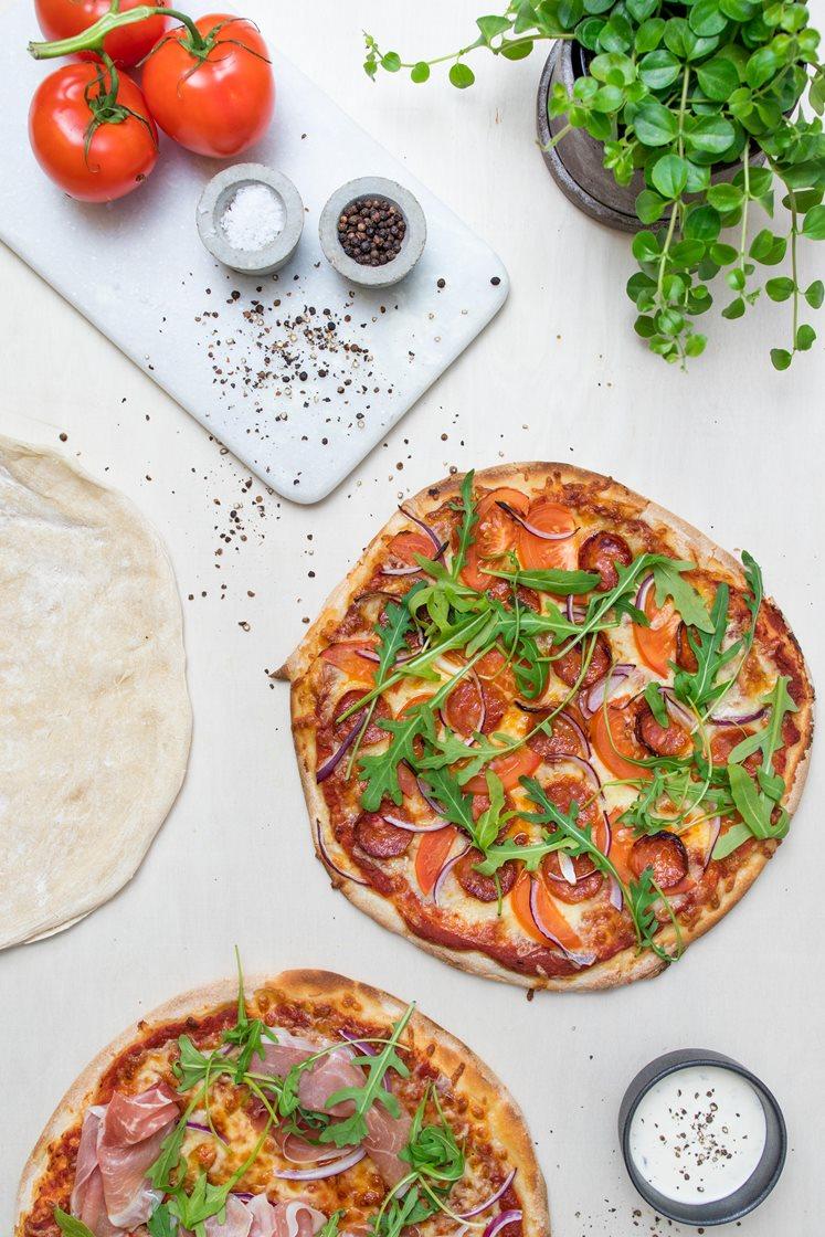 Rød og hvit pizza med mozzarella, parmaskinke og pepperoni på steinovnsbakte pizzabunner