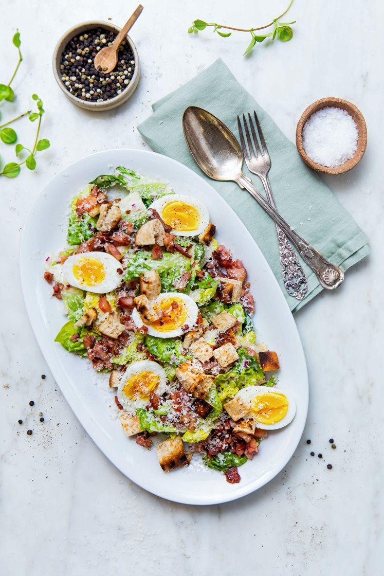 Cæsarsalat med sprøstekt bacon, kokte egg og brødkrutonger, toppet med Grana Padano