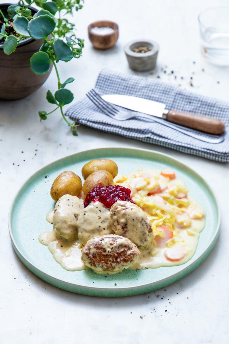 Kjøttkaker i fløtesaus med stuede gulrøtter og kål, servert med kokte småpoteter og rørte tyttebær